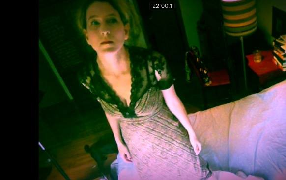 Heathen Derr (Heather Derr-Smith) Film Still. The poet is standing on a bed looking up into a surveillance camera that is watching them. The poet is wearing a ripped lace dress, arms to the side, face in a state of dread or drugged-up expression.