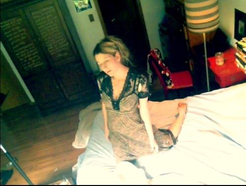 Heathen Derr (Heather Derr-Smith) film still. The poet is on their knees on a bed in a ripped up lace dress, arms hanging limply ton their sides. facial expression is resigned or placid.It looks as though they could be singing quietly.