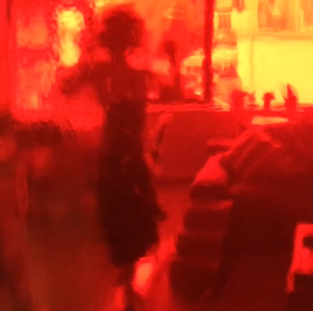 Image is of a film still of Heathen Derr (Heather Derr-Smith) dancing along with the Madison Dance Scene in Bande a Parte by Godard. The camera is filming through a red bottle so everything is tinted red and distorted by the glass.