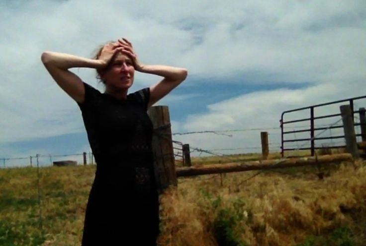 A film still of the poet Heathen Derr (Heather Derr-Smith). The poet is standing in a field at the entrance to a ranch with barbed wire in the background and dry grasses signifying drought. The poet has both hands on their head, elbows jutting out, and a look of distress on their face. There is a big blue sky behind them.