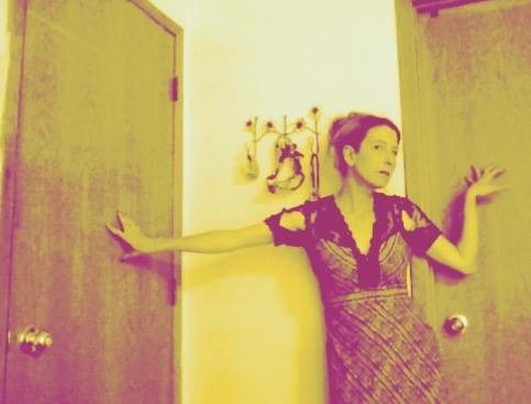 Film still of Heathen Derr (Heather Derr-Smith) The poet is standing  with their back and outstretched arms against two doors with their right arm bent, palm pressed behind them against a door to the right and the left arm reaching out to press the door to the left. The poet is wearing a ripped lace dress. There is the jaw bone of a shark hanging behind them to the left.