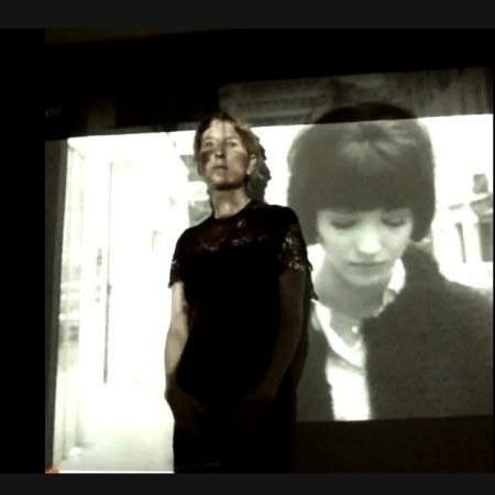 Heathen Derr (Heather Derr-Smith) film still. The poet stands in front of a movie screen upon which the film Vivre sa Vie is being projected. The film is projected also on the poet's body. You can see Anna Karina on the screen behind the poet. The poets face is partially obscured by the projected image but they stare out at something beyond the frame.